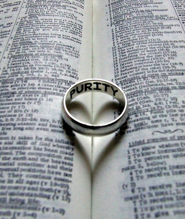 Purity Ring Creating Heart Shadow in Bible.