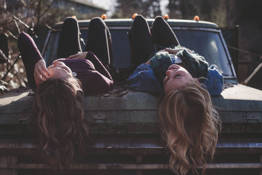 Two college age women sitting on a car hood, talking and looking at the sky.