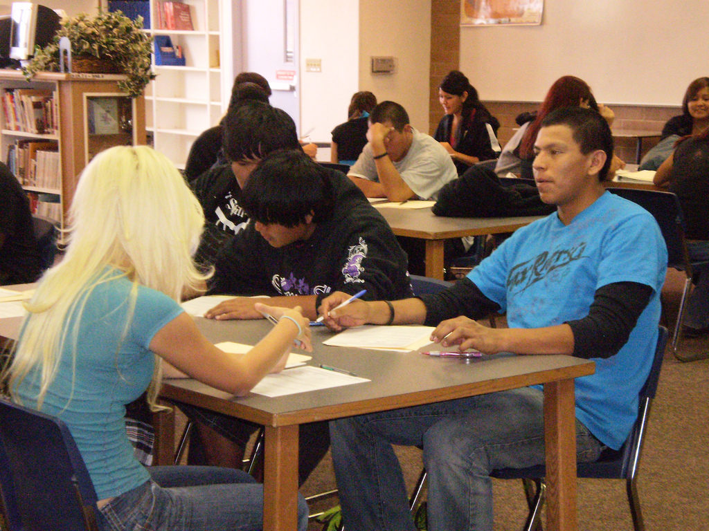 Several teens talking and working at a school table.