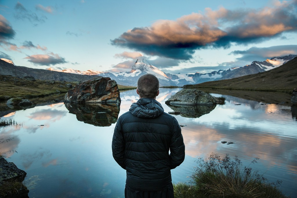 Person facing away looking out over a lake