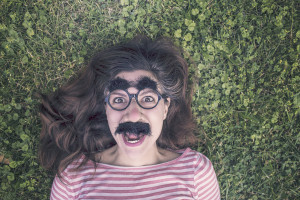 Girl lying on grass with funny glasses on