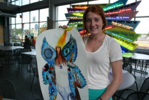 Photo of a student holding her artwork