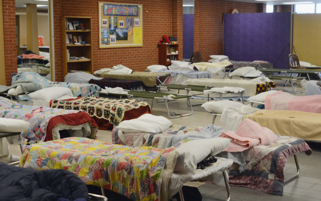 Photograph of empty cots in homeless shelter