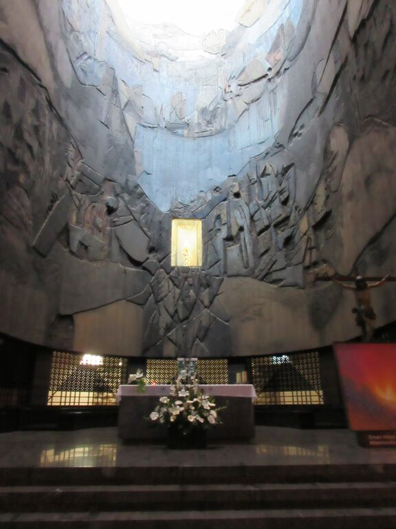 Photo of altar situated in large stone sanctuary