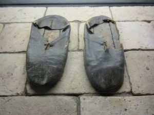 Worn leather shoes resting on brick floor