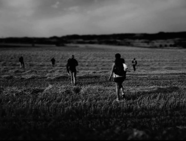 black and white photo of pilgrims walking across grassy field.