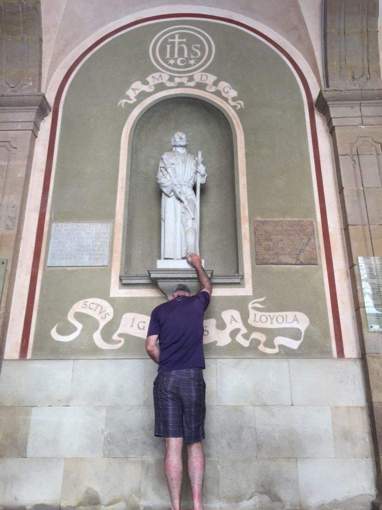 Man standing under statue of St. Ignatus reaching hand up to touch his toe.