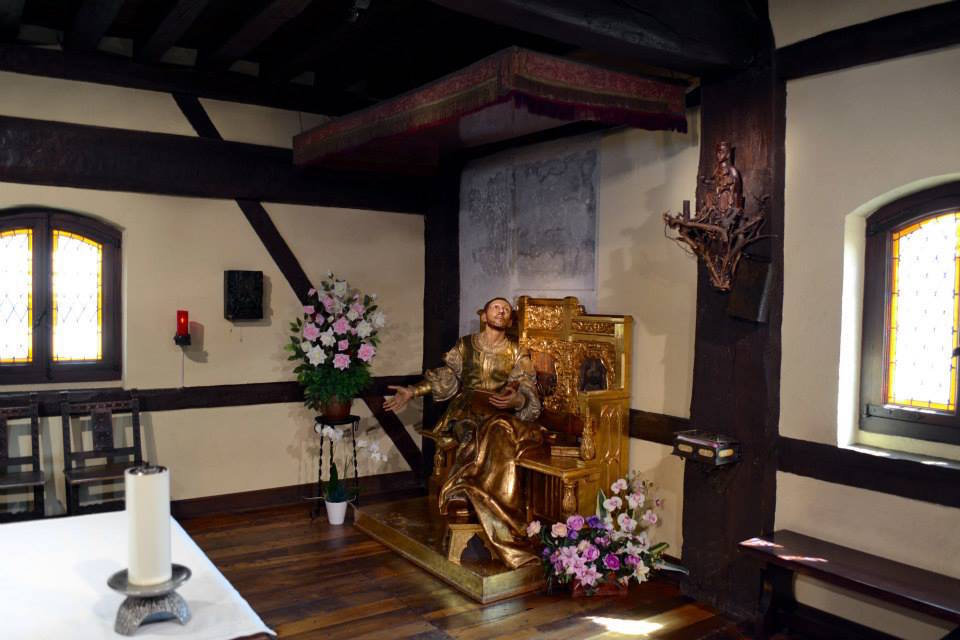 Bronze statue of Ignatius of Loyola seated in a chair in midst of simple room with wood floor.
