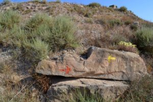 Rock with red arrow pointing right and yellow arrow pointing left.