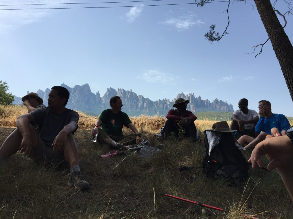 Pilgrims resting with jagged mountains in the backround.