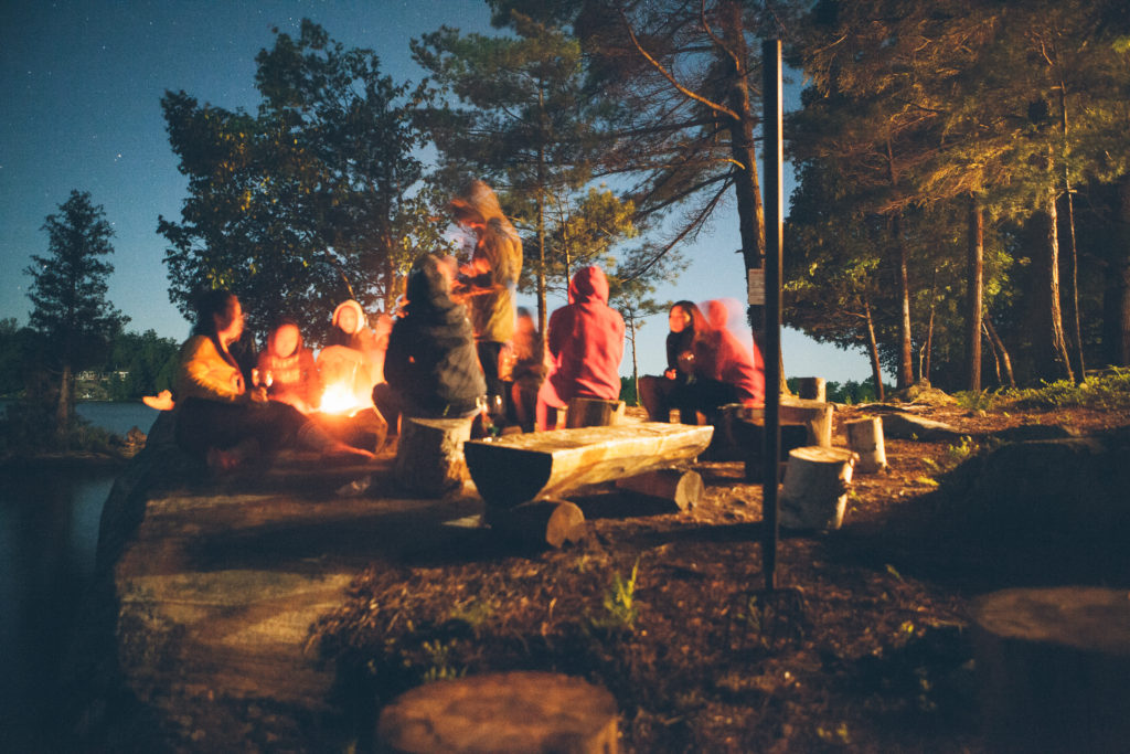 People gathered around a campfire at dusk