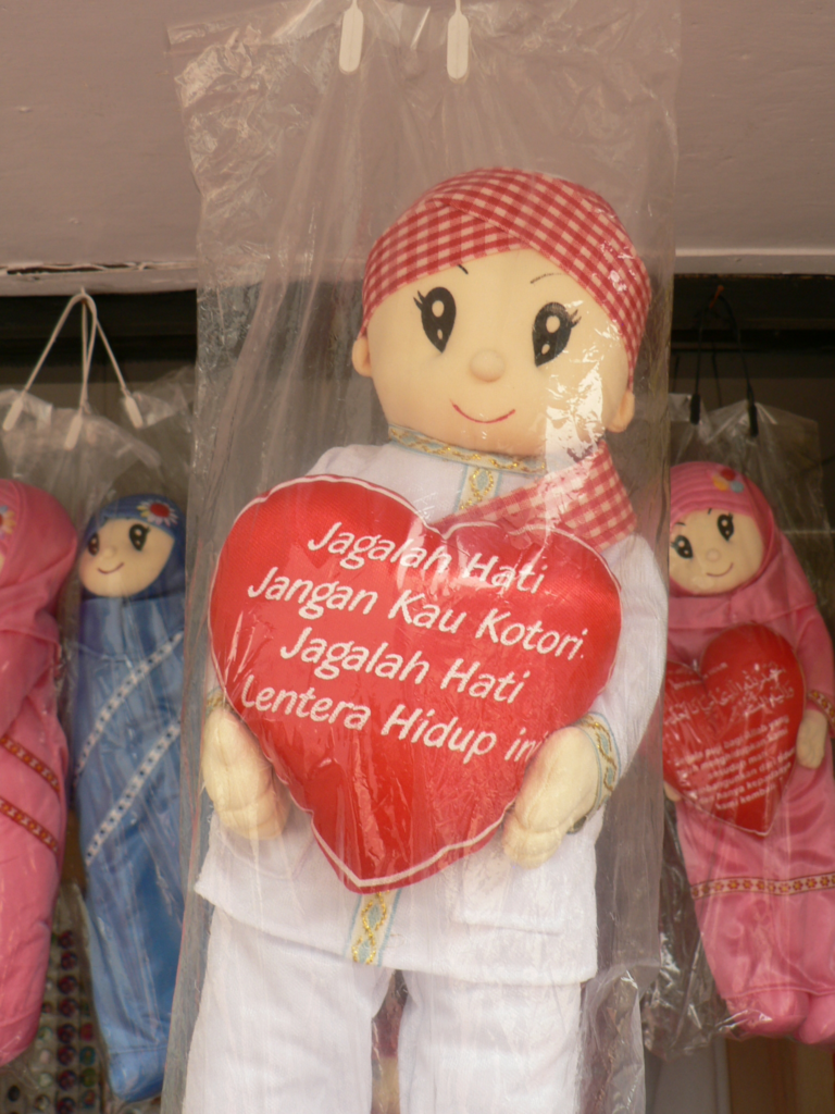 Cloth doll holding a heart with writing on it.