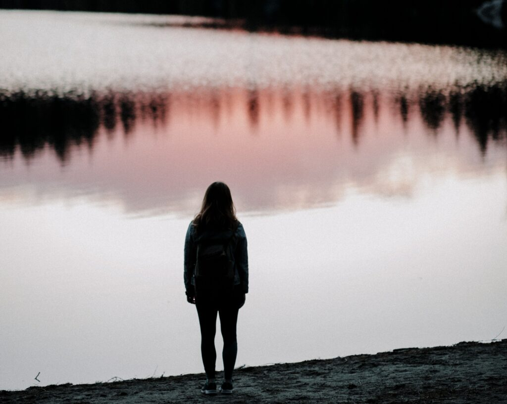 Silhouette of girl looking at lake at twilight