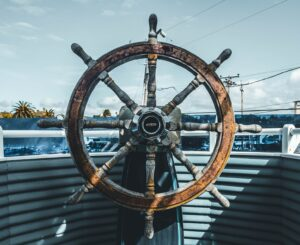 Closeup image of an old ship's wheel, looking out the front of the boat.