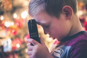 Child praying with a Bible in hand